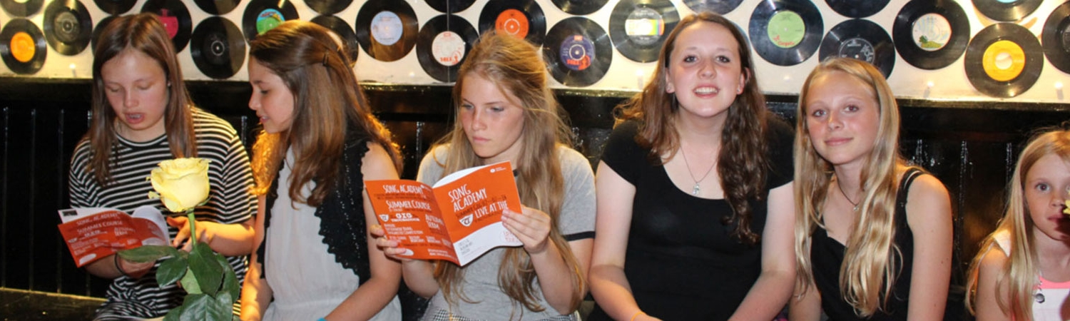 a group of girls reading the Song Academy brochure